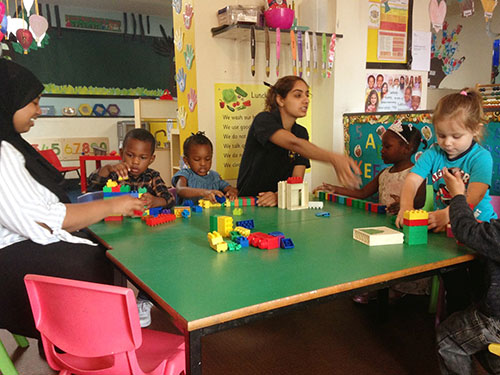Two nursery nurses with children playing with building blocks